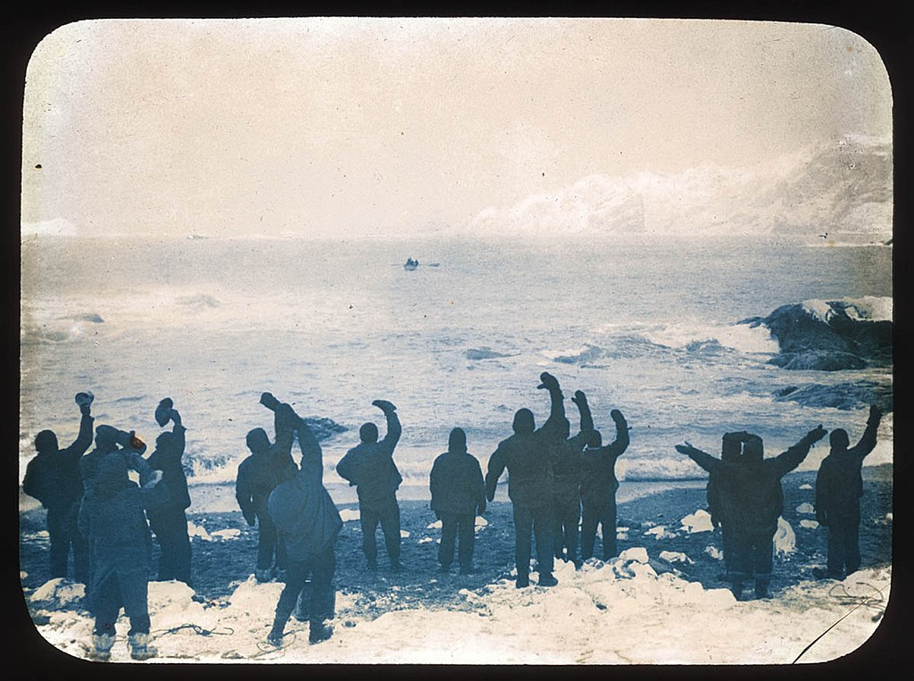 Elephant Island party waving goodbye to boat across Arctic sea